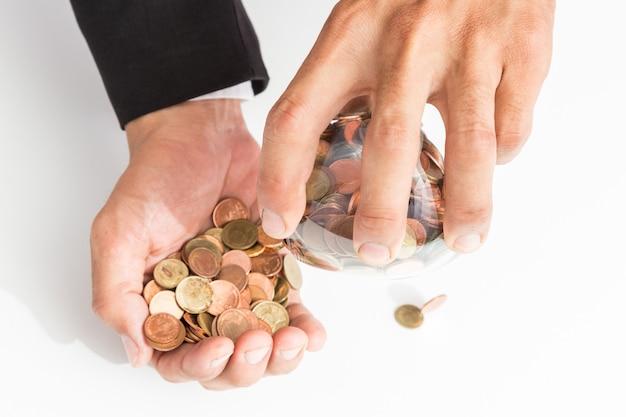 Kaufmann gießt münzen aus dem glas in seine hand,