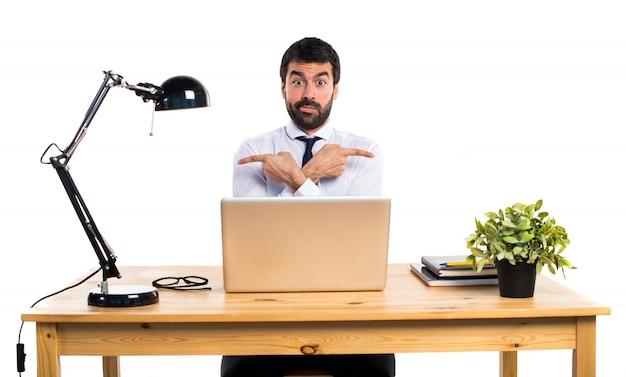 Kaufmann in seinem büro zeigt auf die seiten mit zweifeln