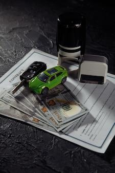 Kaufvertrag für ein auto mit briefmarken, schlüsseln und spielzeugauto. vertikales bild