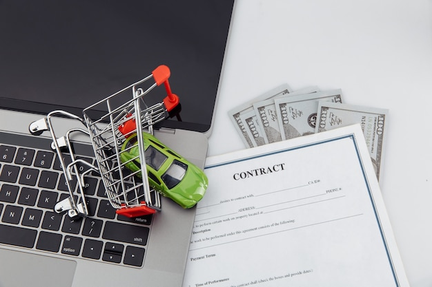 Kaufvertrag für ein auto mit laptop, geld und spielzeugauto im einkaufswagen.