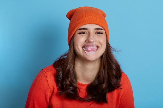 Kaugummiblase, die auf gesicht der glücklichen lachenden frau kleidet, kleidet pullover und mütze und posiert isoliert auf blau