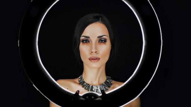 Kaukasier hinter einer kreisförmigen lampe für porträtfotoaufnahmen