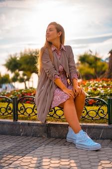 Kaukasier und blondine mit kastanienbraunem regenmantel und blumenkleid in der stadt. attraktives junges mädchen mit der sonne im hintergrund neben blumen in einem schönen park