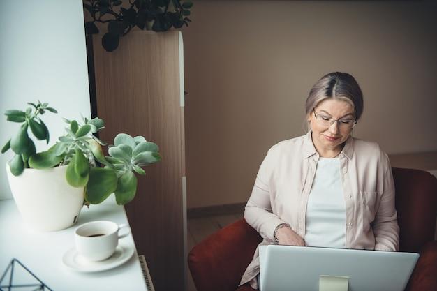 Kaukasische ältere blonde geschäftsfrau, die von zu hause am laptop beim trinken eines kaffees arbeitet