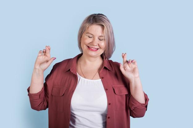 Kaukasische ältere frau mit blonden haaren denkt an etwas, das lächelt und finger auf einer blauen studiowand kreuzt