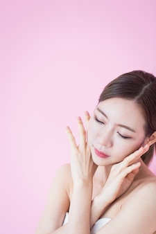 Kaukasische asiatische frau berühren ihr sauberes frisches hautgesicht. kosmetologie, hautpflege, plastische chirurgie und spa-therapiekonzept