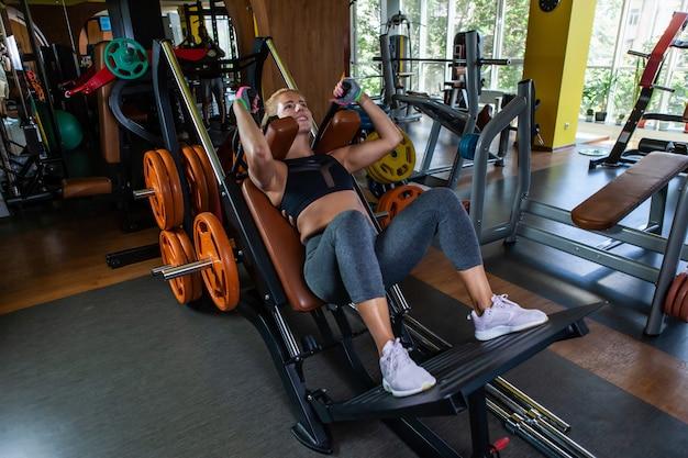 Kaukasische attraktive frau, die kniebeugen im trainingsgerät im fitnessstudio übt