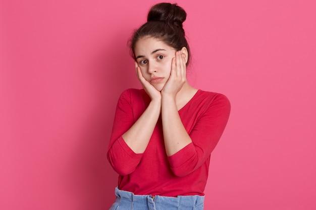 Kaukasische attraktive junge frau, die rotes stilvolles hemd, dame mit haarknoten trägt