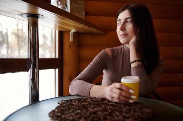 Kaukasische attraktive junge frau, die trinkenden tee entspannt, während sie nahe am fenster in der hölzernen cafébar sitzt