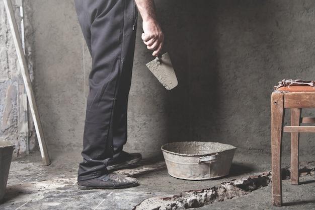 Kaukasische bauarbeiter verputzen wand bauarbeiten