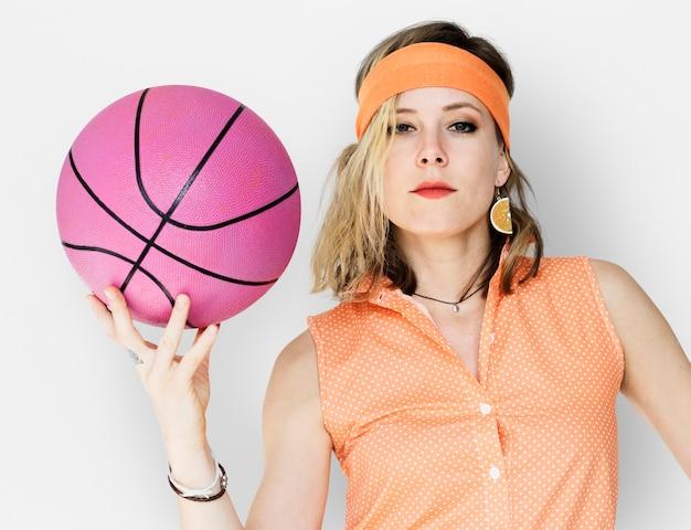 Kaukasische blonde frau, die basketball hält