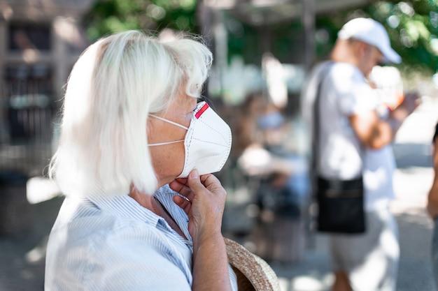 Kaukasische blonde frau, die schutzmaske gegen das neue 2019-ncov coronavirus an einem öffentlichen bahnhof trägt