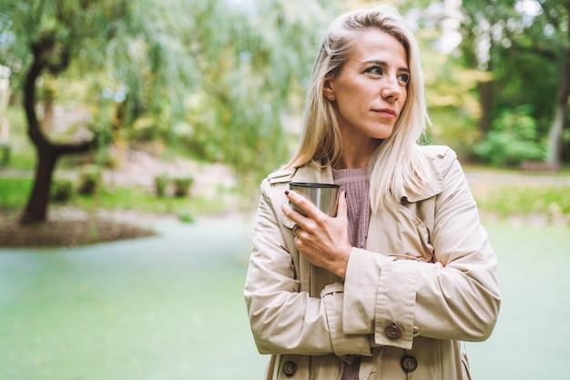 Kaukasische blonde frau geht im grünen park an einem sonnigen sommer- oder frühlingstag mit einer tasse heißem getränk.