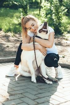 Kaukasische blonde frau und ihr goldener retriever, die während eines spaziergangs im park umarmen
