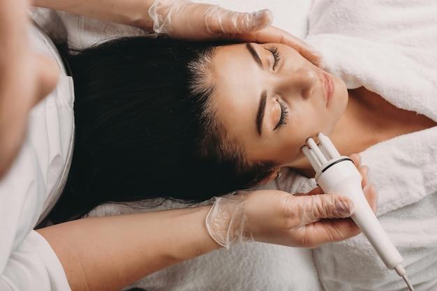 Kaukasische brünette, die ein hautpflegeverfahren beim liegen auf der couch in einem spa-salon hat