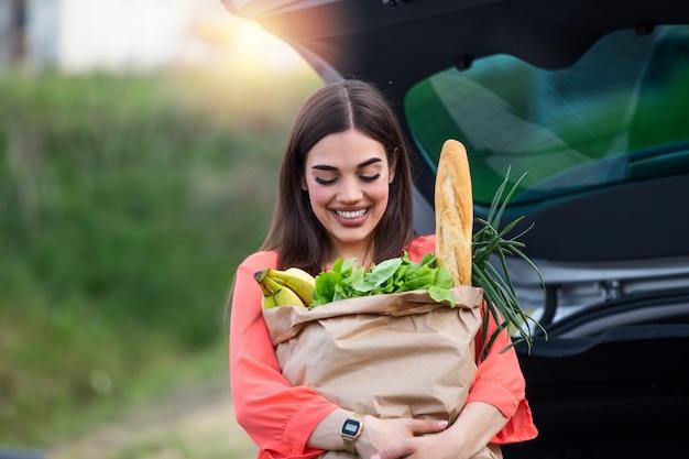 Kaukasische brünette, die papiertüten mit nahrungsmitteln hält. junge frau, die paket mit lebensmitteln und gemüse in autokofferraum setzt.