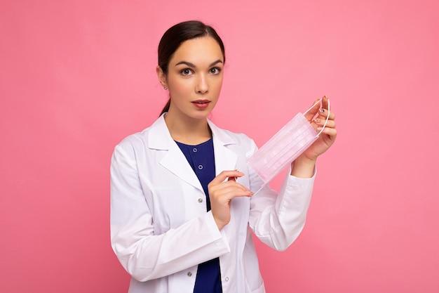 Kaukasische brünette frau mit schutzmaske isoliert auf rosafarbenem hintergrund coronavirus oder