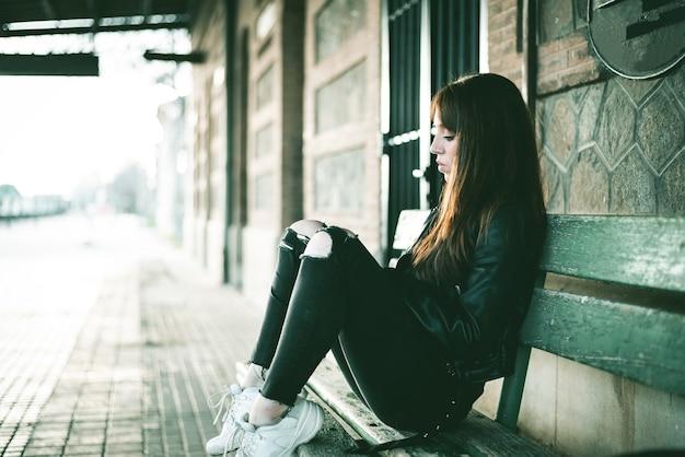 Kaukasische brünette frau sitzt auf der bank hinter einem gebäude und wartet auf den zug