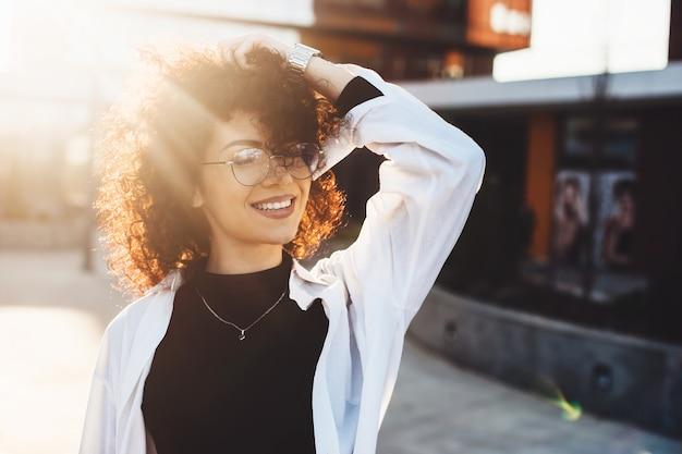 Kaukasische charmante frau mit dem lockigen haar, das ihren kopf berührt, während sie mit brille draußen aufwirft