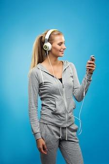 Kaukasische dame des schönen blonden sitzes im grauen sport mit hörender musik der kopfhörer. isoliert auf blaue wand