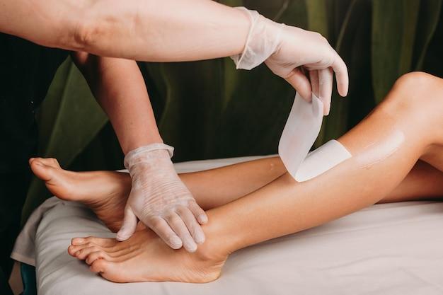 Kaukasische dame, die in einem spa-salon wartet, um ihre wachssitzung auf beinen zu beenden