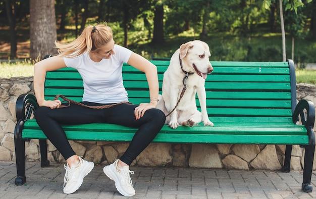 Kaukasische dame und ihr labrador posieren im park auf einer bank, die eine pause vom gehen hat