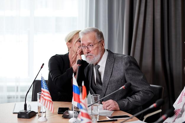 Kaukasische delegierte, die meinungen über die rede ihrer kollegin austauschen, erwachsene frauen sprechen etwas im ohr eines älteren grauen bärtigen mannes im anzug und diskutieren