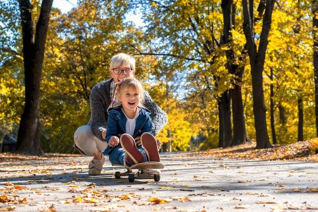 Kaukasische enkelin, die den tag mit großmutter genießt, während sie ein skateboard im park reitet