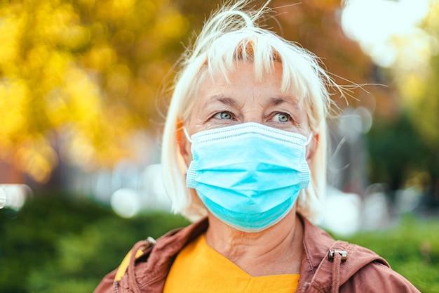 Kaukasische erwachsene blonde frau 50 jahre alt in hellem gewand und schützender medizinischer atemschutzmaske, die sich auf dem parkhintergrund umschaut