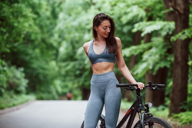 Kaukasische ethnizität. weiblicher radfahrer, der mit fahrrad auf asphaltstraße im wald am tag steht