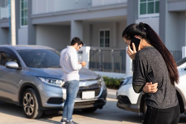 Kaukasische fahrerin, die nach einem verkehrsunfall einen anruf beim versicherungsagenten tätigt. unfall. kfz-versicherung ein nichtlebensversicherungskonzept.