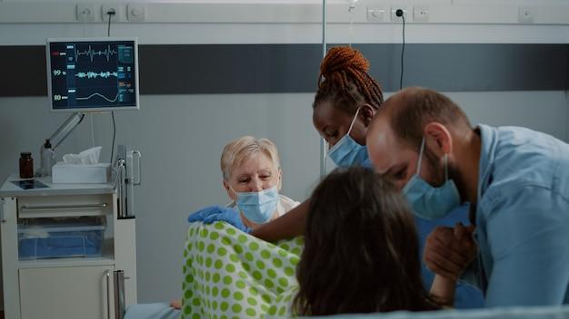 Kaukasische familie bei der geburtsarbeit, die medizinische hilfe im krankenbett erhält. geburtshilfe-arzt und afroamerikanische krankenschwester helfen schwangeren frauen, die auf die geburt eines kindes drängen