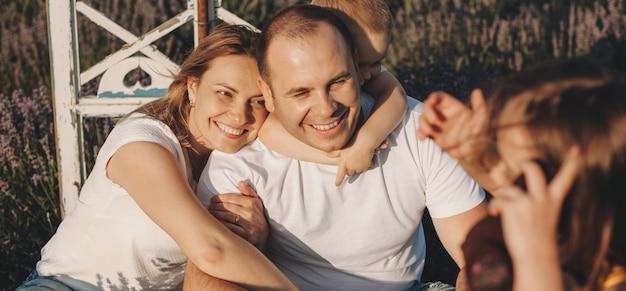Kaukasische familie, die in einem lavendelfeld sitzt, das an einem sonnigen tag lächelt und umarmt