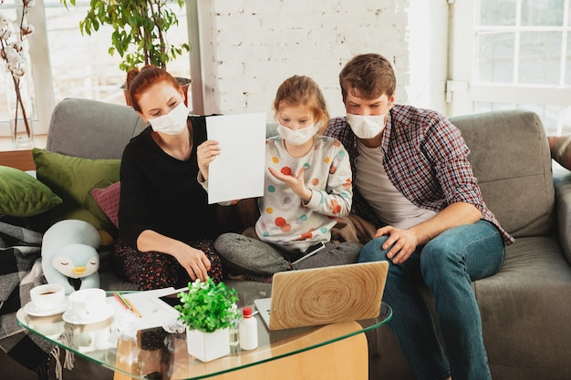 Kaukasische familie in gesichtsmasken und handschuhen, die zu hause mit coronavirus-atemwegssymptomen wie fieber, kopfschmerzen, husten in mildem zustand isoliert sind. gesundheitswesen, medizin, quarantäne, behandlungskonzept.