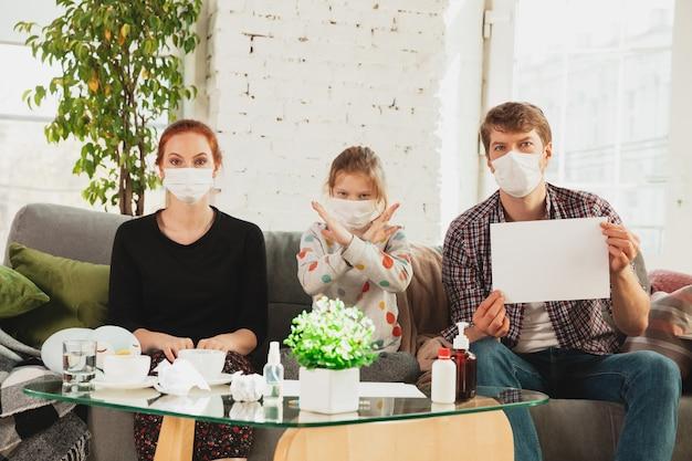 Kaukasische familie in gesichtsmasken und handschuhen, die zu hause mit coronavirus isoliert sind