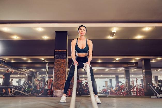 Kaukasische fit frau gekleidet im sportoutfit, das mit kampf aufwirft