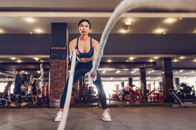 Kaukasische fit frau gekleidet in sportausstattung, die mit kampfseilen am fitnessstudio aufwirft