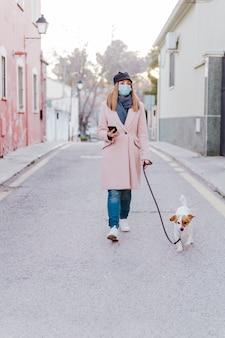 Kaukasische frau auf der straße, die schutzmaske trägt und mit ihrem hund geht. corona-virus-konzept