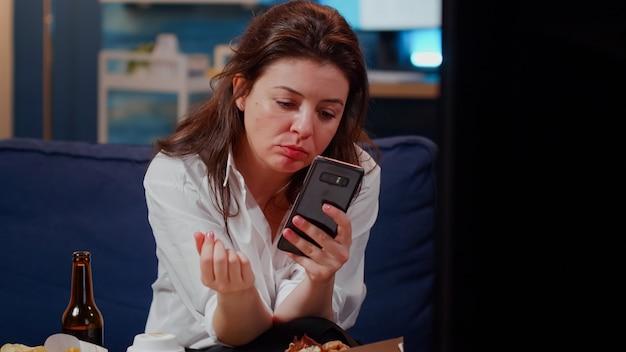 Kaukasische frau beißt ein stück pizza und hält smartphone