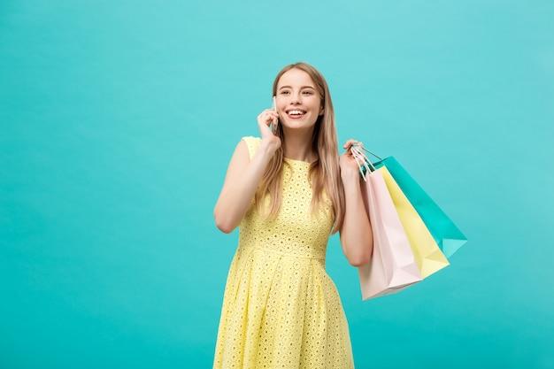 Kaukasische frau der glücklichen mode mit einkaufstaschen um handy ersuchend.