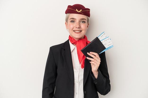 Kaukasische frau der jungen stewardess, die den pass lokalisiert auf weißem hintergrund glücklich, lächelnd und fröhlich hält.