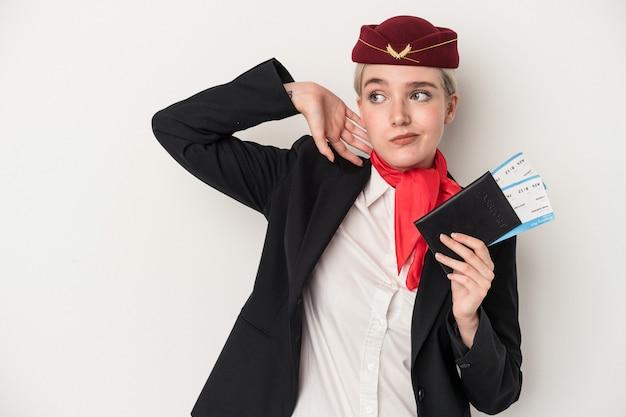 Kaukasische frau der jungen stewardess, die den pass lokalisiert auf weißem hintergrund hält, der den hinterkopf berührt, denkt und eine wahl trifft.