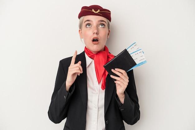 Kaukasische frau der jungen stewardess, die den pass lokalisiert auf weißem hintergrund hält, der oben mit geöffnetem mund zeigt.