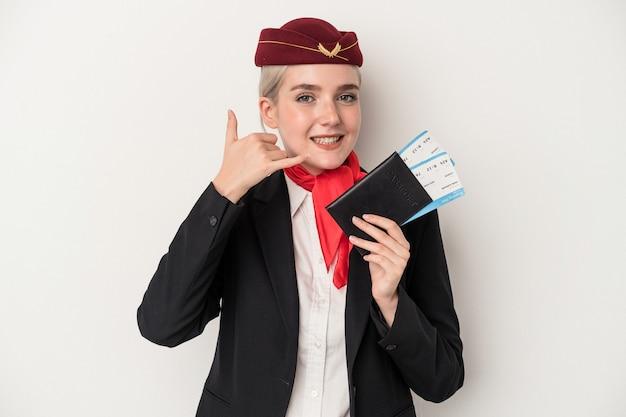 Kaukasische frau der jungen stewardess, die den reisepass lokalisiert auf weißem hintergrund hält, der eine handyanrufgeste mit den fingern zeigt.