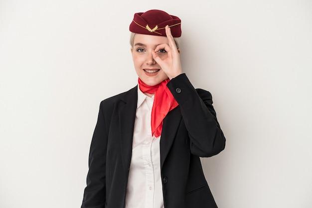 Kaukasische frau der jungen stewardess lokalisiert auf weißem hintergrund aufgeregt, ok geste auf auge zu halten.
