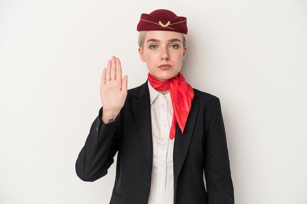 Kaukasische frau der jungen stewardess lokalisiert auf weißem hintergrund, die mit ausgestreckter hand steht, die stoppschild zeigt und sie verhindert.
