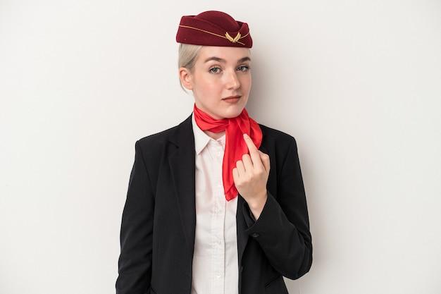 Kaukasische frau der jungen stewardess lokalisiert auf weißem hintergrund, die mit dem finger auf sie zeigt, als ob sie einladen, näher zu kommen.