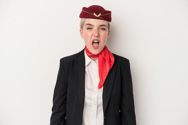 Kaukasische frau der jungen stewardess lokalisiert auf weißem hintergrund, die sehr wütend und aggressiv schreit.
