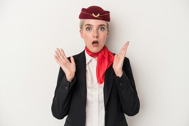 Kaukasische frau der jungen stewardess lokalisiert auf weißem hintergrund überrascht und schockiert.