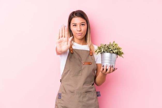 Kaukasische frau des jungen gärtners lokalisierte stellung mit der ausgestreckten hand, die das stoppschild zeigt und verhinderte sie.